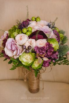 Lavender and purple roses and ranunculus were used for the bridal bouquet. | www.BridalBook.ph