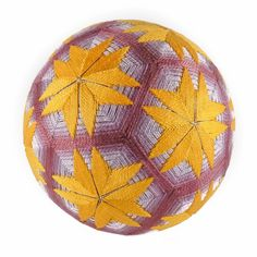 "This is a complex 10 division that results in 12 ""faces"" being created.  Golden, multi-point stars burst over shades of purple. This temari is an  all-over design, where the surface of the ball (mari) is completely covered  by embroidery.   Size: 4.6"" diameter  Materials: Rice husks, fiberfill, yarn, sewing thread, embroidery thread,  rattle  Shown with wood stand."
