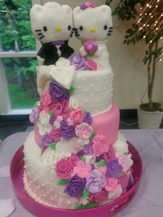 Hello kitty wedding cake with fondant covered rice krispy molded toppers and a cascade of flowers. Made by Jesseeeee :)
