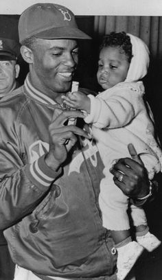 Jackie Robinson, of the Brooklyn Dodgers, holds his son Jackie Jr. (not sure of the year)