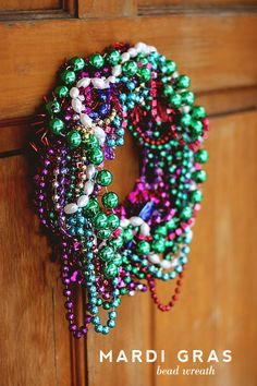 Tomorrow is Fat Tuesday, which makes this the Monday before Mardi Gras, aka Lundi Gras.Time to get our bead on.Hot pink wreath from Dollar Store + pipe cleaners + a whole lot of throw beads = instant wreath.Total time: 10 minutesTotal Cost: $1 (would have been more if I didn't have a pre-existing bead problem)…