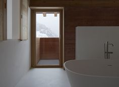 Rothaus | Jonathan Tuckey Design, Andermatt, Switzerland. Red pigmented, board marked concrete walls, with a white natural plaster finish. A large corian bathtub seamlessly integrates within the aesthetic of the room.