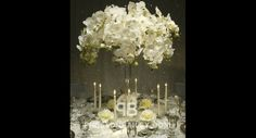 White Floral Centerpiece with Tall Candles - candles, centerpiece, flowers, orchid, reception, roses, round tables, tall centerpiece, color ...