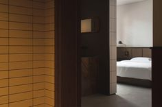 The dark walnut panelling is continued inside the rooms and used on furniture and window shutters, while off-white rectangular tiles, white bed linen and brown leather create a lighter mood. Yellow Tile, Pink Tiles, Chinese Interior, Wooden Facade, Earthy Color Palette, Bauhaus Style, Leather Headboard, Relaxing Places, Chengdu