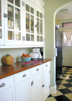 love everything about this kitchen...glass panel cupboard doors, latches on doors, butcher block counter tops and beading backboard....the checkered floors--not so much!
