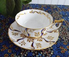 This is a beautiful all hand paintedEnglish cup and saucer made by Royal Chelsea, England 1951-1961 in a strikingdesign of gold leaves and swirls with cobalt