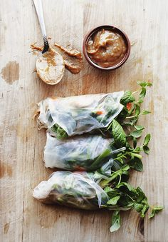 Summer rolls with pulled pork, quick pickled vegetables, fresh mint and peanut butter dip.