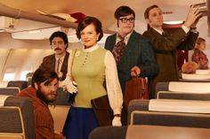 Stan Rizzo (Jay R. Ferguson), Michael Michael Ginsberg (Ben Feldman), Peggy Olson (Elisabeth Moss), Harry Crane (Rich Sommer) and Ken Cosgrove (Aaron Staton) board a plane wearing some serious late-'60s duds. Harry wears a large paisley tie, while Stan sports a fringed jacket and a full-on beard.