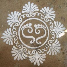 Pongal Kolam Design - This design is fairly simple & its only done using white powder. This design is in circular shape. The floral designs are done around the circle & the center holds the design of the footprints of the Goddess of Prosperity, Laxmi. The Goddess Laxmi is believed to be the one who provides humans w/ Money. The Goddess blesses humans w/ good crops & the way to earn one's livelihood. The design is a simple & great way to celebrate the blessings of Laxmi upon you.