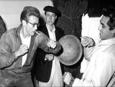 A behind the scenes shot of Hollywood legend James Dean sparring with visitor/friend Parry Lopez as co-star Nick Adams looks on during filming of the classic 1955 drama, REBEL WITHOUT A CAUSE!