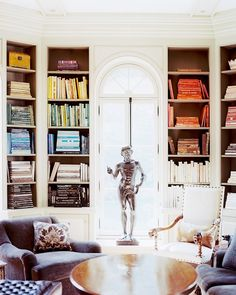 White shelving walls with colorful books, statue, grey furniture, wooden coffee table, white arm chair