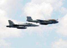ATLANTIC OCEAN (July 24 2010) An EA-6B Prowler assigned to the Patriots of Electronic Attack Squadron (VAQ) 140 and an F/A-18F Super Hornet assigned to the Jolly Rogers of Strike Fighter Squadron (VFA) 103 flies by the aircraft carrier USS Dwight D. Eisenhower (CVN 69). The Eisenhower Carrier Strike Group is deployed as part of an on-going rotation of forward-deployed forces to support maritime security operations in the U.S. 5th and 6th Fleet areas of responsibility. (U.S. Navy photo by…