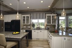 Painted cabinetry with weathered wood island in this rustic chic kitchen give a warm welcome feeling. Industrial vintage ceiling wood beams  with pendant lighting.