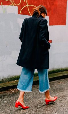 Street style look sobretudo preto, calça culotte jeans e sapato verniz vermelho.