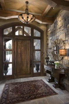 Rustic Entryway with Tiffany shotgun shell inverted pendant, quartz floors, Transom window, Grand palais console table
