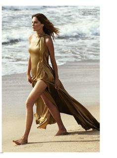 American model Erin Wasson is a beach beauty as she poses in the April 2015 cover story from Harper's Bazaar Russia.  Erin looks as glamorous as ever in a gold Ralph Lauren Collection dress.