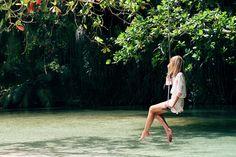 garota pensativa sentada em um balanço na árvore sobre um rio.