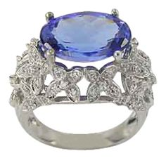 Large Oval Tanzanite Set Sideways In Antique Diamond Ring -  This antique inspired tanzanite diamond ring has a 5.72ct oval blue tanzanite center stone and is adorned with 0.70cts of bright round diamonds.   Brilliant white diamonds are set in small floral units. The flowers encircle the center oval tanzanite, giving the impression of a nest of diamonds. The characteristics of antique rings are milgrain, antique engraving and filigree.   Our rings have thick and durable shanks which will...