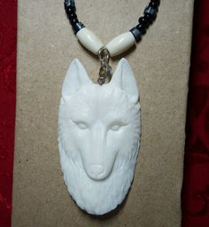 Handmade Native American necklace featuring detailed wolf carving of bone.