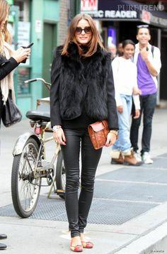 Pour se tenir chaud, elle craque pour le gilet en fourrure qu'elle porte sur son blazer habituelle. Une paire de ballerine colorées et une pochette camel casse le total look dark.
