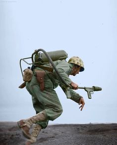 A US Marine flamethrower operator moves forward to assault a Japanese pillbox on Motoyama Airfield, Iwo Jima. ca. Feb-Mar 1945.  ('E' Company, 2nd Battalion, 9th Marines, 3rd Marine Division on or near February 26 1945)  This Marine carries an M2-2 portable flamethrower and his personal armament includes a large fighting knife and a .45 automatic pistol.  (Photo source - Department of Defense Photo (USMC) 111006.)  (Colorized by Jared Enos from the USA)…