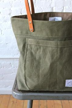 Sturdy, worn-in canvas salvaged from a WWII era US military duffel bag has been turned into a perfect everyday tote bag. Features a large outer pocket made from