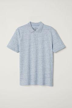 Polo azul claro jaspeado de manga corta en punto de algodón con cuello con botones y aberturas laterales.