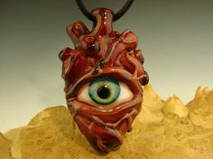 """Flameworked BORO GLASS """"Eye of the Heart"""" Pendant Lampworked (flameworked) with durable and scratch resistant Borosilicate (Pyrex) Glass made by Kenny Talamas at Vortex Glassworks size: 2 and 3/8 inches (60mm) tall by 1 and 1/4 inches (32mm) wide with a 1/4 inch (6mm) bale (hole in the loop on top) """"Eye of the Heart"""" Pendant -a realistic-style human heart with an eye peering out from the center. The glass is blood red with metallic rust colored 'veins' on the surface and back of the pendant…"""