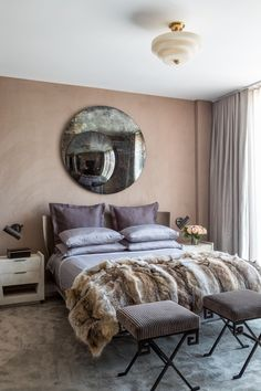 """""""It's probably my favorite room in the place,"""" says Dedivanovic of the master bedroom. """"It feels very rich and warm and reminds me of being in a great hotel—but even better because it's so personal to me, and my own."""" Korban warmed up the modern lines of a B&B Italia bed with an oxidized mirror by Michael Dawkins Home, a fur throw from Area ID, and walls upholstered in J. Robert Scott suede. Sconces by Apparatus Studio hover above custom end tables, and commissioned X-base stools inspired by…"""