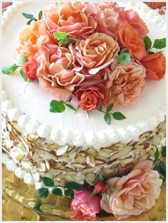 White iced cake with almonds and roses.... simple for a garden party!