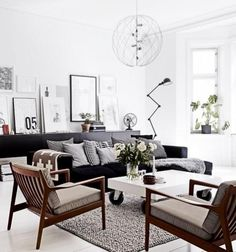 Beautiful scandinavian style living room with white walls,framed wall art and white coffee table on wheels