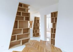 Wooden bookshelves installed against slanted walls help to define the different areas of this open-plan loft apartment.