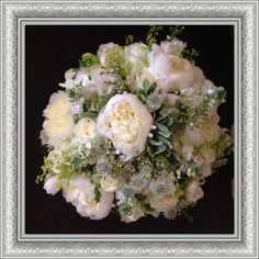 All white Brides Bouquet containing white Peonies, Roses, Freesia and some luscious lime and sage green Foliage.