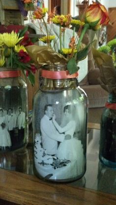 Our table centerpieces for my in laws 50th wedding anniversary. A large Mason jar, a 5X7 photo, gold tissue paper and flowers. They were adorable!