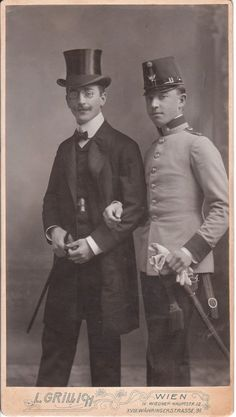 The subjects are two very interesting looking young men. One man is wearing a tuxedo and top hat. He is holding a cane and wearing eyeglasses. The second young man appears to be wearing a formal military uniform. He is holding white gloves and wearing a sword. There is likely an interesting story attached to this photograph but that story is lost to history.