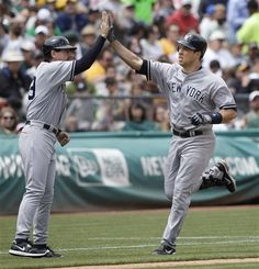 GAME 46: Saturday, May 26, 2012 - New York Yankees' Mark Teixeira, right, celebrates with third base coach Rob Thomson after hitting a solo home run off of Oakland Athletics pitcher Bartolo Colon during the fourth inning of a baseball game in Oakland, Calif. (AP Photo/Jeff Chiu)