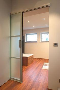 Glazen design schuifdeur op maat gemaakt door Anyway Doors. De gebruikte materialen zijn gezuurd glas en aluminium.