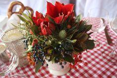 Winterhochzeit, Winter weddding, center piece, Tischdekoration mit Amaryllis, Disteln, Beeren, Hagebutten in Steingutbechern auf rot-weiß karierten Tischdecken