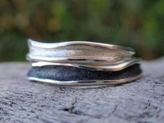 This is a handmade set of two wedding bands or stacking rings in sterling silver with a wavy shape. The rings are highly polished and the hollow part has a brushed finish as if water runs through it. The channel of the bottom ring is black oxidized and the other one is in the natural color of sterling silver. The ring set is crafted with the ancient method of lost wax completely by hand to this shape.width: 2.5mm to 3.1mmThe rings can be ordered in the same or two different sizes.Please...