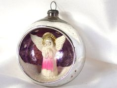 This vintage silver Japan glass angel diorama indent Christmas holiday ornament has a 3D angel scene in the indent. The plastic angel...