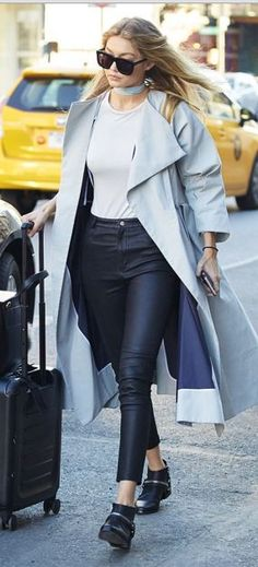 Who made  Gigi Hadid's black handbag, top, sunglasses, gray coat, ankle boots, and leather pants?