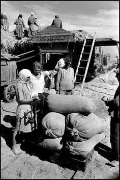 Robert Capa © International Center of Photography View profile USSR. 1947. Bringing in the bags of wheat on Shevchenko. (Collective Farming).