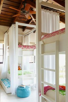Chic cottage kids' room features a plank ceiling accented with a fan over two sets of bunk beds fitted with trundle beds dressed in otomi bedding and white curtain panels.