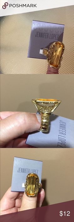 "Jennifer Lopez expandable gold tone ring This is a NWT expandable gold tone ring. The front of the ring has two peach colored ""stones"" to give a great look. Fits many different sizes.   Smoke free home and no Pay Pal please. Jennifer Lopez Jewelry Rings"