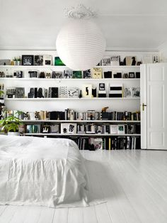 In this chic home from Studded Heart, black decor lines the shelves of a white bedroom for a contrasting color scheme.