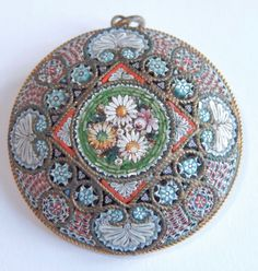 Fresh from a fine Northwest estate comes a large antique gold gilt silver micro mosaic pendant brooch circa 1900. The piece is very well made and features an intricate design with a cluster of flowers at center.