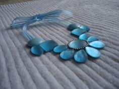 Maxi colar azul claro, chatons em formatos variados, gotas, ovais, quadrados e redondos. Chaton redondo central contornado com corrente de bolinhas na cor niquel. Fecho em fita de organza azul clara. R$42,90