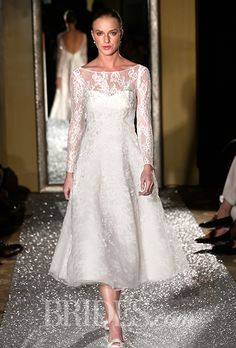 Brides: Oleg Cassini - Fall 2015. Style CWG663, long sleeve lace and organza tea-length A-line wedding dress with an illusion neckline and beaded lace appliqués, Oleg Cassini