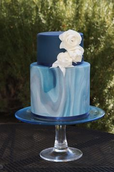 Blue tiered marbled wedding cake with white roses