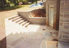 Basement Entrance steps leading down to a small slat patio into basement.